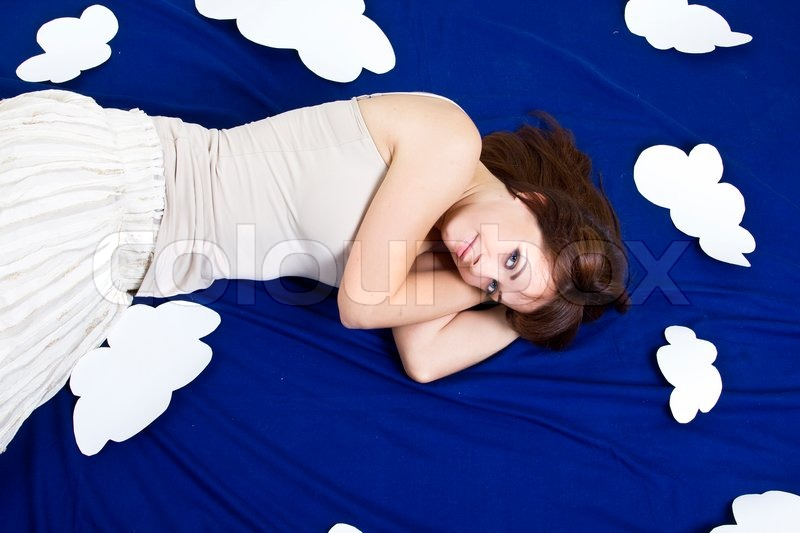 Girl lying in clouds, stock photo