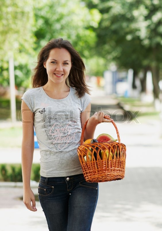 The young smiling girl staying with the basket, stock photo