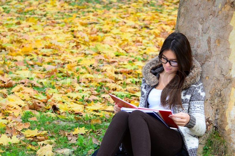 beautiful bru te girl reading book in nature stock