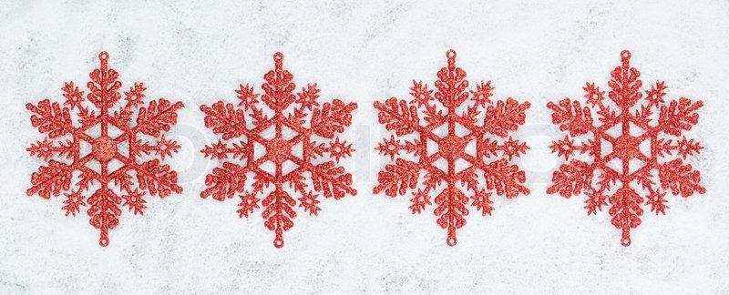 four decorative christmas snowflakes closeup on snow stock photo