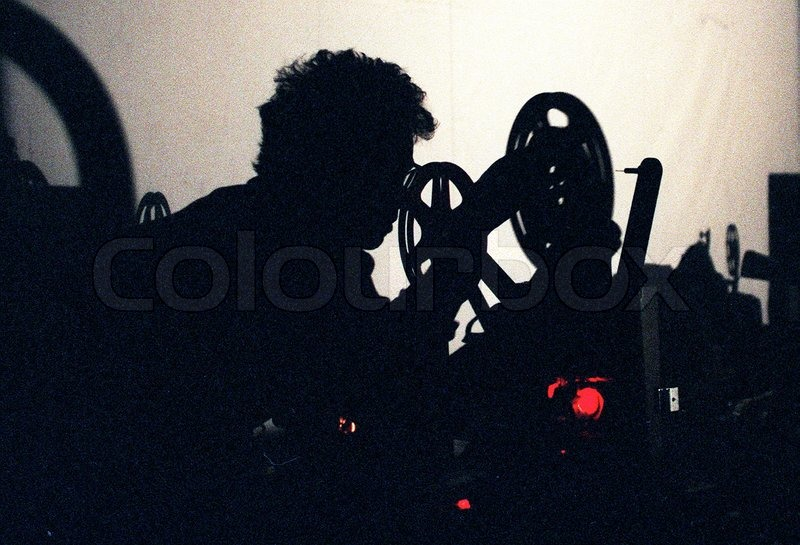 Stock image of 'Silhouette of a man with a projection machine'