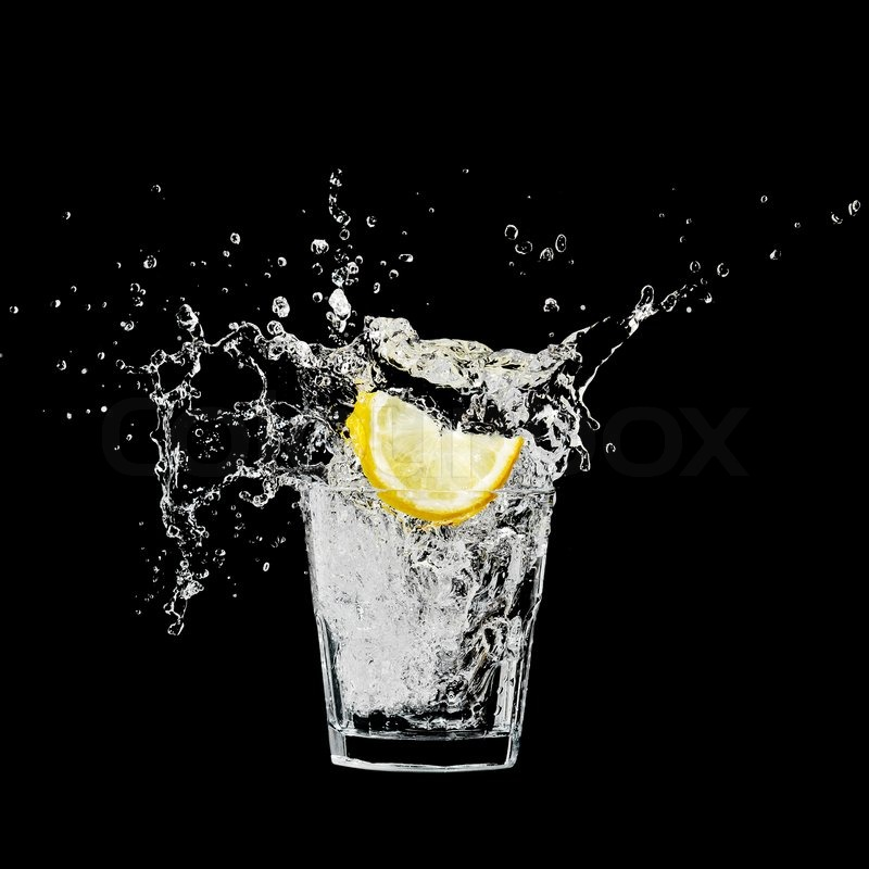 Splash In A Glass With Lemon And Ice On A Black Background