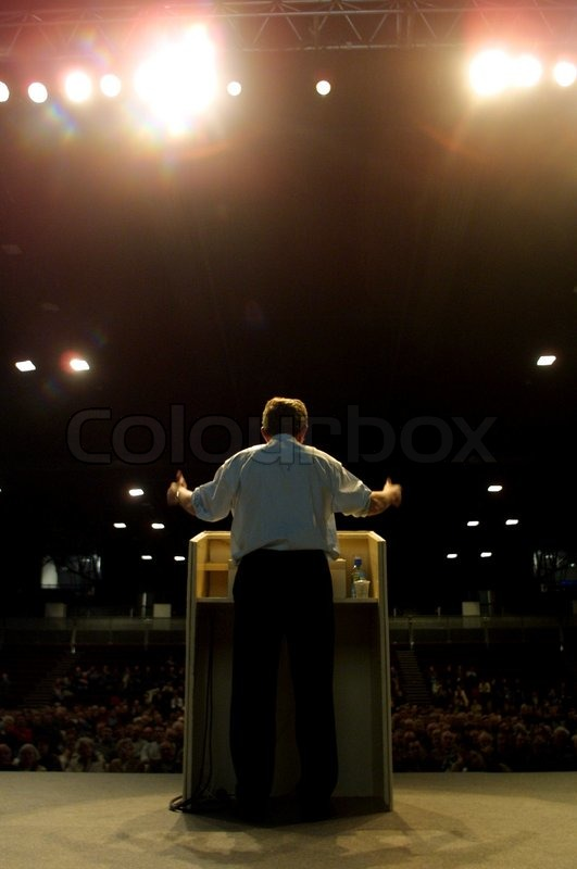 Rear view of man giving speech from stage to people ...
