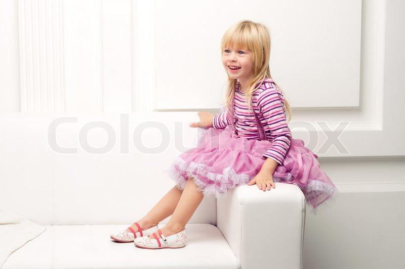 Little girl posing happily on sofa, stock photo.