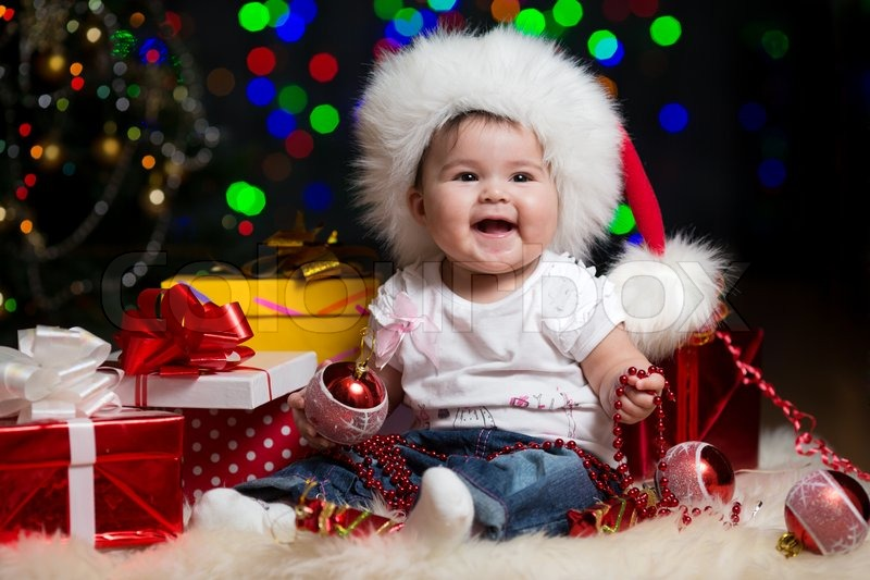 baby girl in santa claus hat with gifts under christmas tree stock photo colourbox