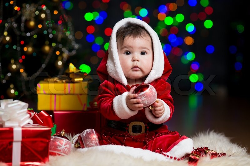 Kid girl dressed as Santa Claus near Christmas tree with gifts ...