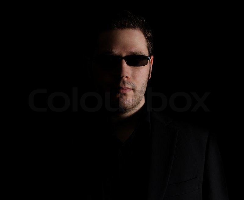 Portrait of man in black suit on black background, stock photo