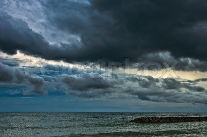 Big rain cloud over the calm sea and rock, stock photo