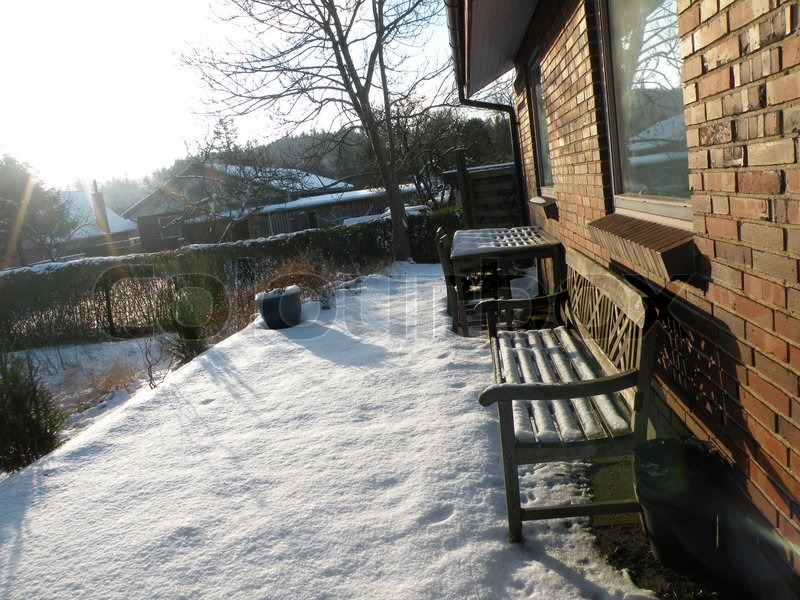 Snow on the terrace of a danish house with bench under the for Danish terrace