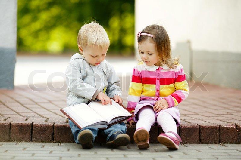 cute boy and girl reading a book stock photo colourbox