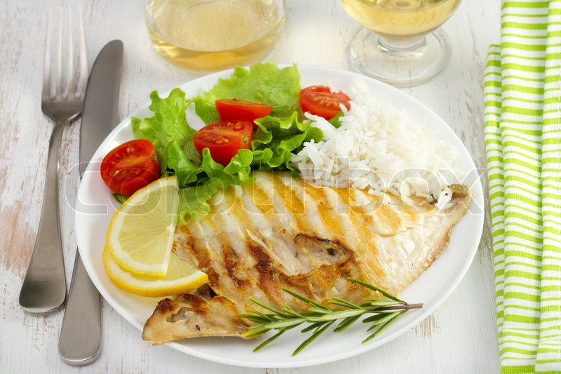 Grilled fish with rice ans salad on the white plate for Fish and rice diet