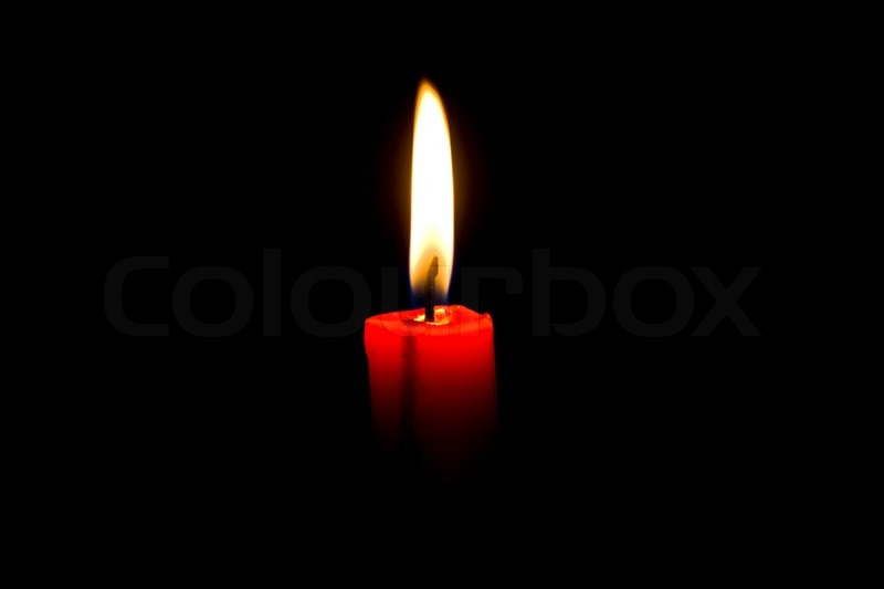 Closeup of burning red candle isolated on black background ...