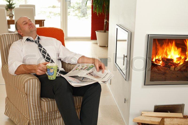 Stattlichen Mitte Erwachsenen Mann Ruht Nach Der Arbeit Mit Tasse Kaffee  Und Täglich Neben Kamin Im Wohnzimmer, Stock Foto