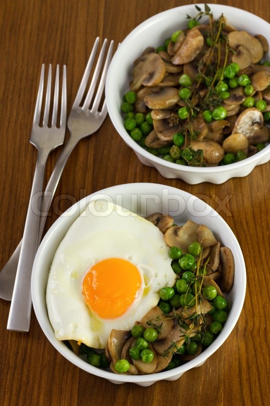Stock image of 'Fried egg with peas with mushrooms in dishes and forks ...