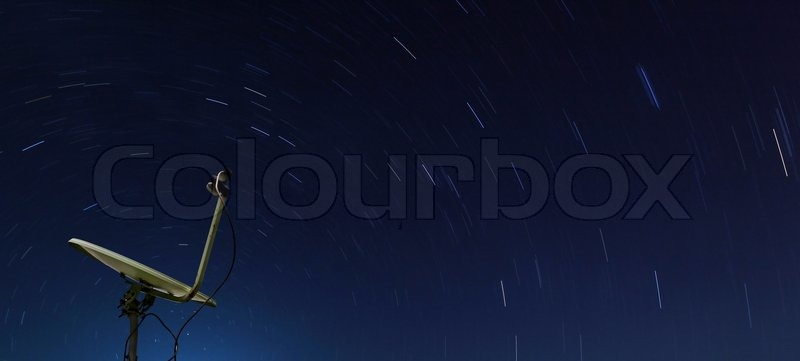 Conceptual of yellow satellite over spiral star at night, stock photo