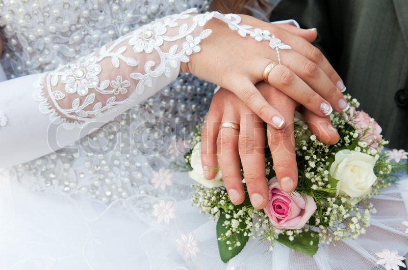 Hands and rings on wedding bouquet, stock photo