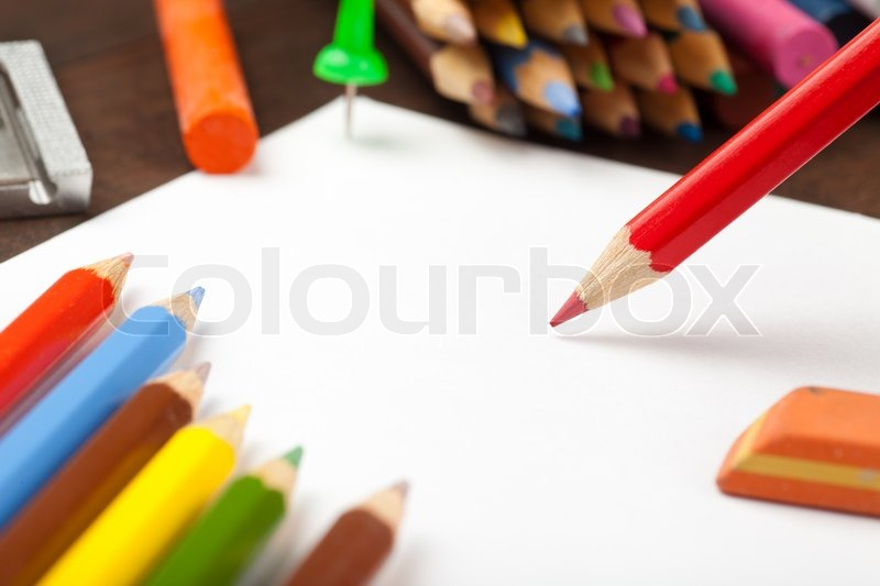 Red pencil draws on white paper sheet Colored pencils, crayons, eraser on table, stock photo