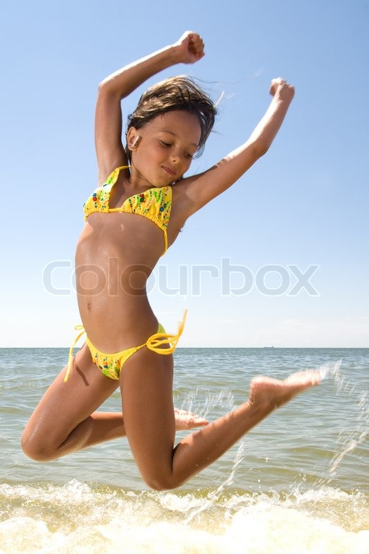 Little girl jumping at the sea | Stock Photo