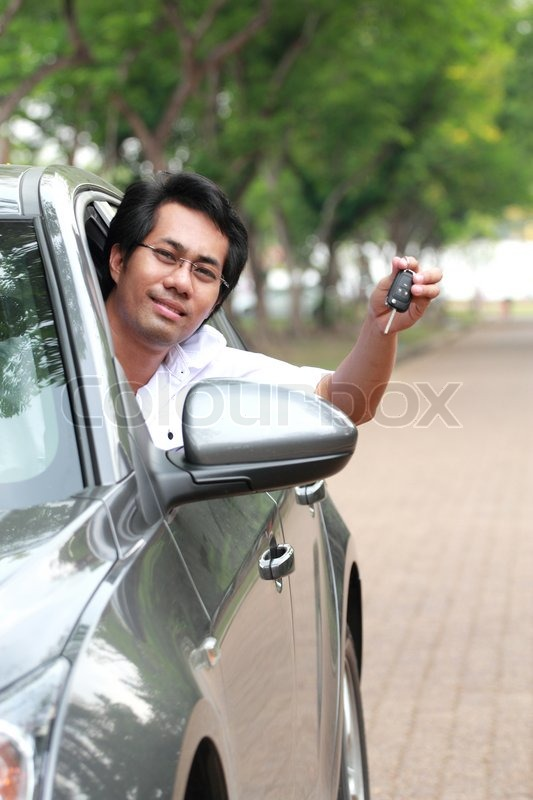 Young man in the car show the key, stock photo