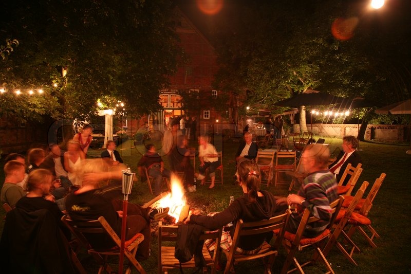 People sitting around fireplace in garden at night