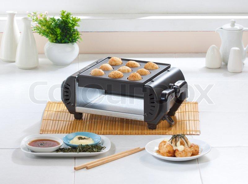 takoyaki japanese food making machine auf dem k chentisch stockfoto colourbox. Black Bedroom Furniture Sets. Home Design Ideas