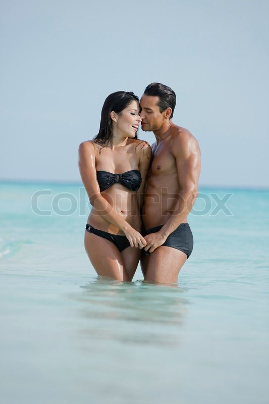 couple romancing in water on the beach stock photo colourbox