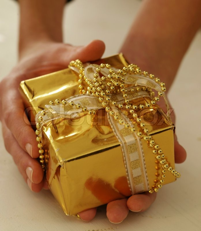 Stock image of 'A female hand holden a Christmas present'