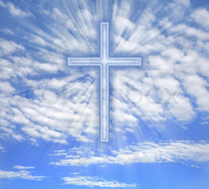christian cross with light beams over sky