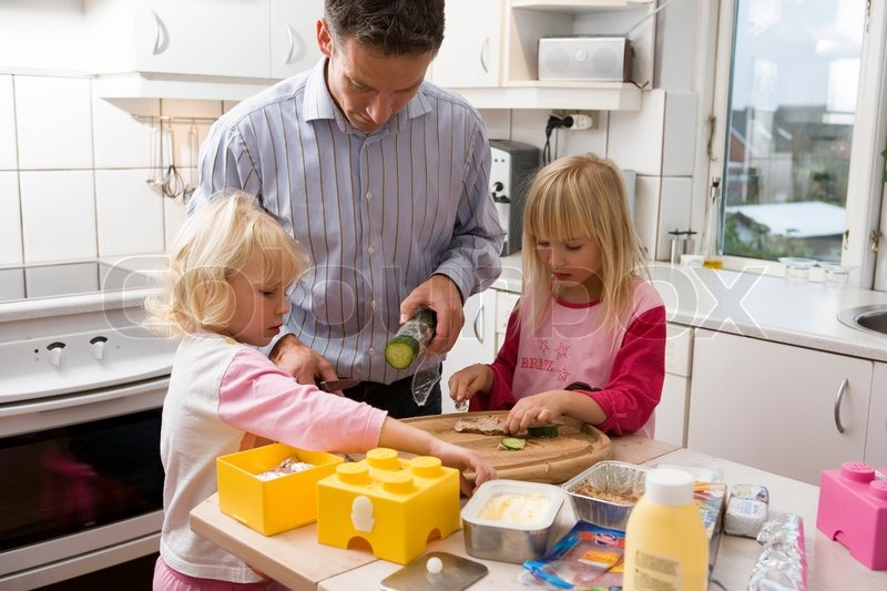 A single father preparing school lunch with his daughters, stock photo