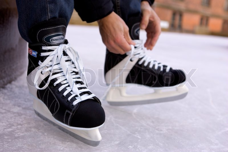 Cropped image of a person tying ice skates, stock photo
