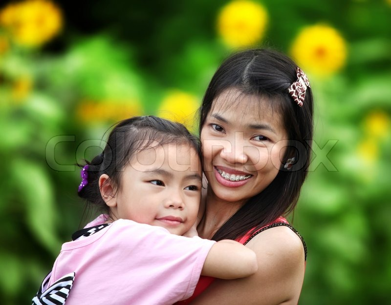 Stock image of 'Happy familymom and baby playing against sumflower background in summer park'