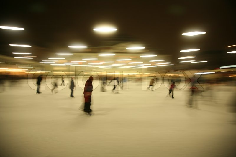 Stock image of 'Blurred image of people skating on ice rink at night'