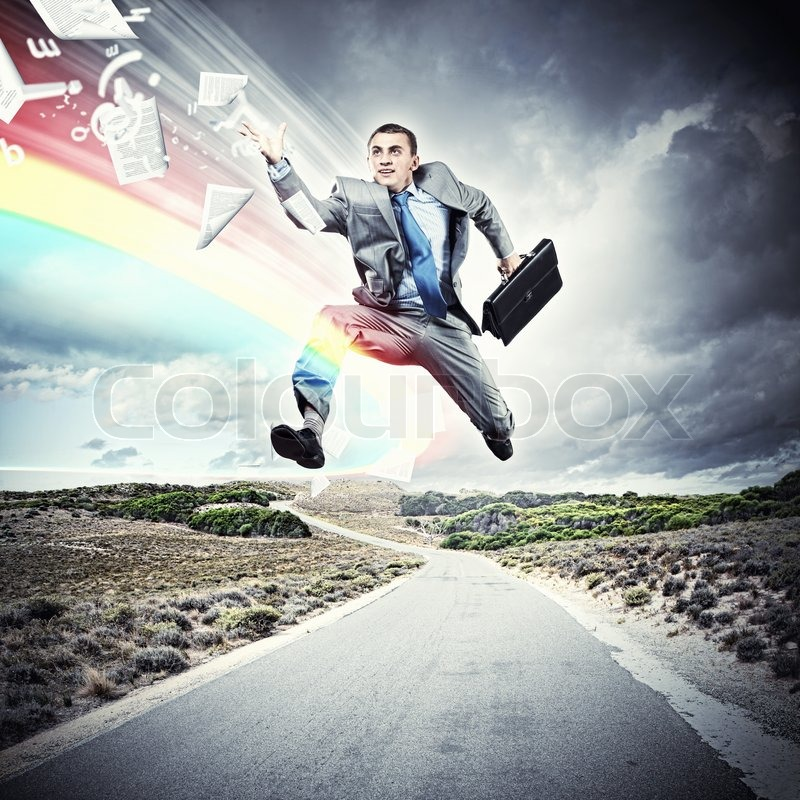 Young businessman in suit running on the road, stock photo