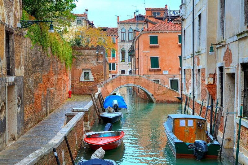 Boats on narrow canal among old colorful brick houses and small bridge on background in Venice ...