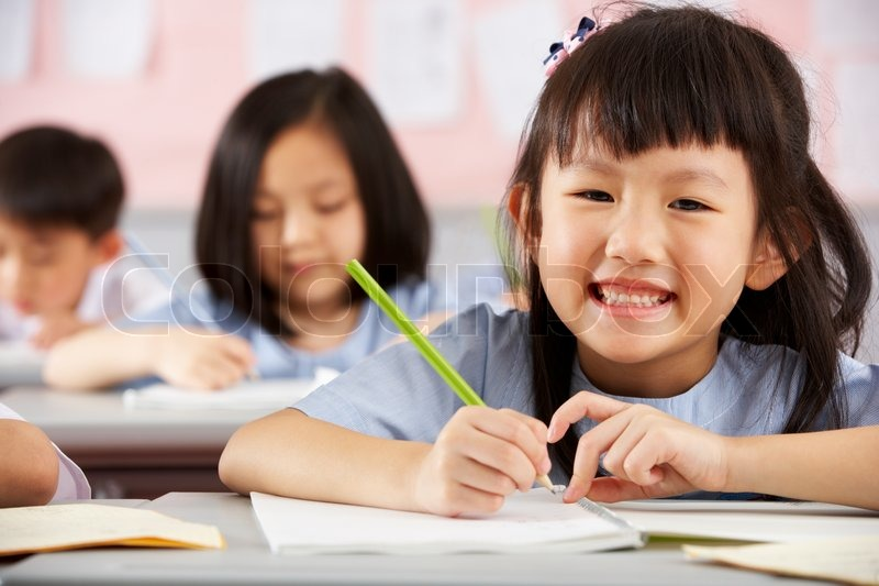 Group Of Students Working At Desks In Chinese School Classroom, stock photo