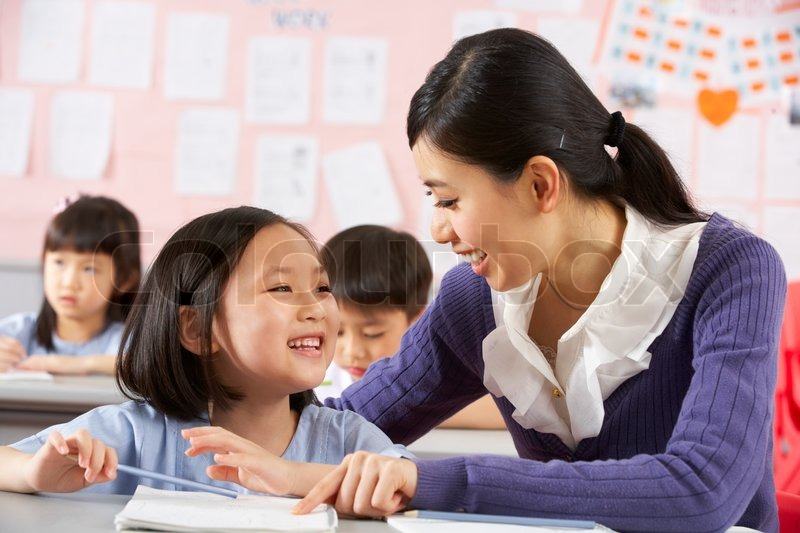 Teacher Helping Student Working At Desk In Chinese School Classroom, stock photo
