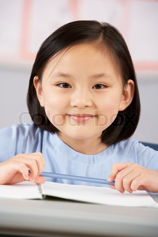 Female Student Working At Desk In Chinese School Classroom, stock photo