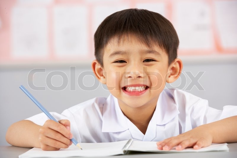 Male Student Working At Desk In Chinese School Classroom, stock photo