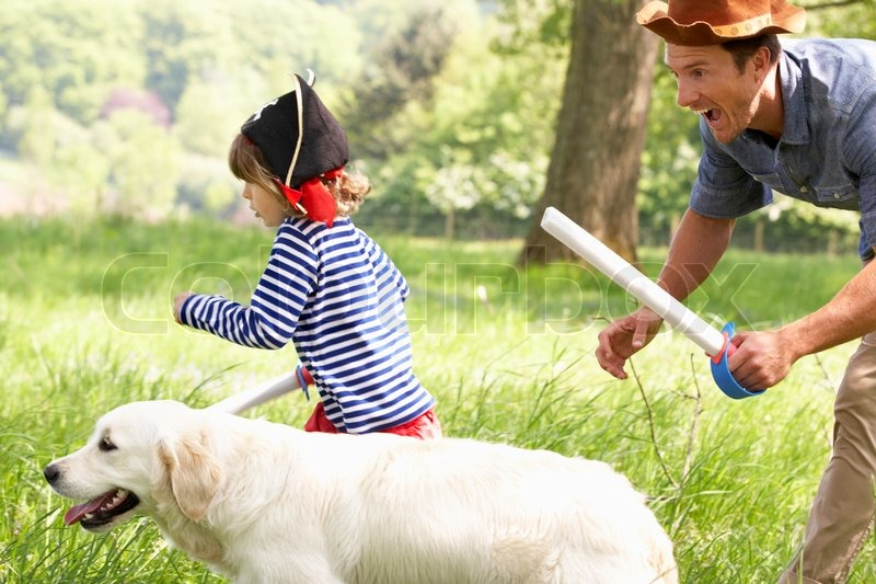Father Playing Exciting Adventure Game With Son And Dog In Summer Field, stock photo