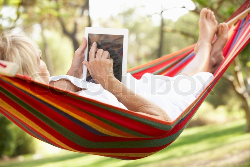 Stock image of 'Senior Woman Relaxing In Hammock With  E-Book'