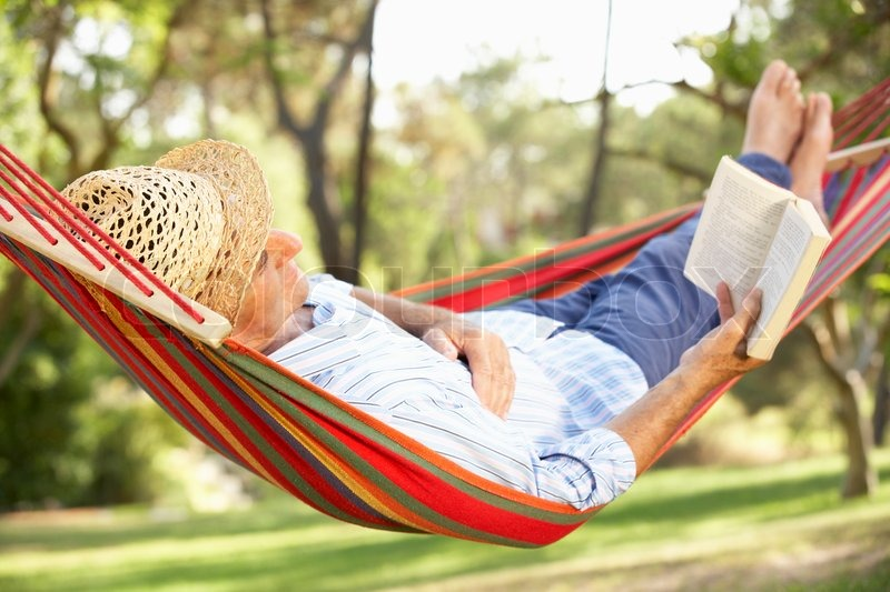 Stock image of 'Senior Man Relaxing In Hammock With Book'