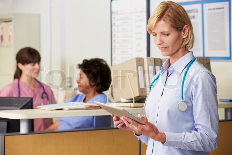 Female Doctor Reading Patient Notes At Nurses Station, stock photo