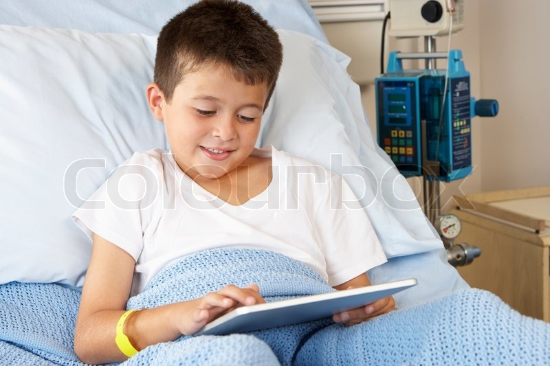 Boy Relaxing In Hospital Bed With Digital Tablet, stock photo