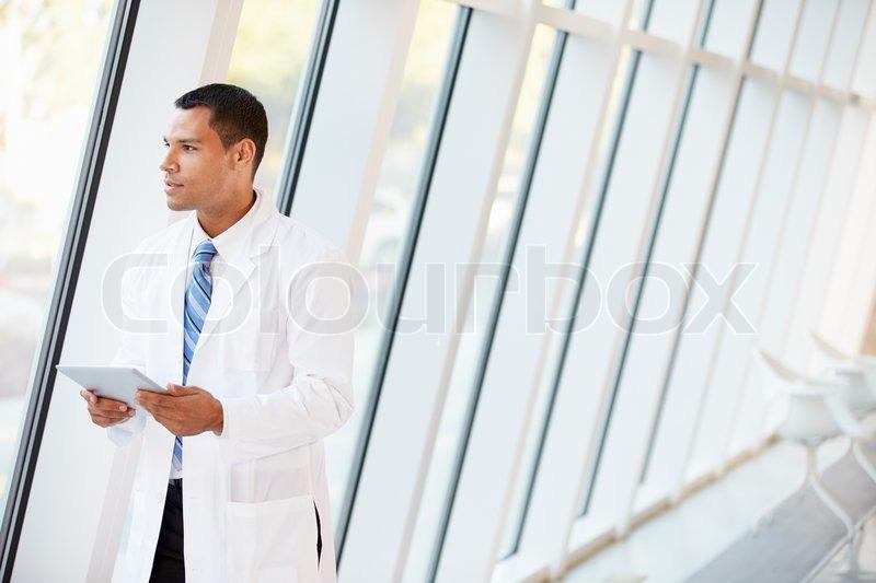 Doctor Using Digital Tablet In Corridor Of Modern Hospital, stock photo