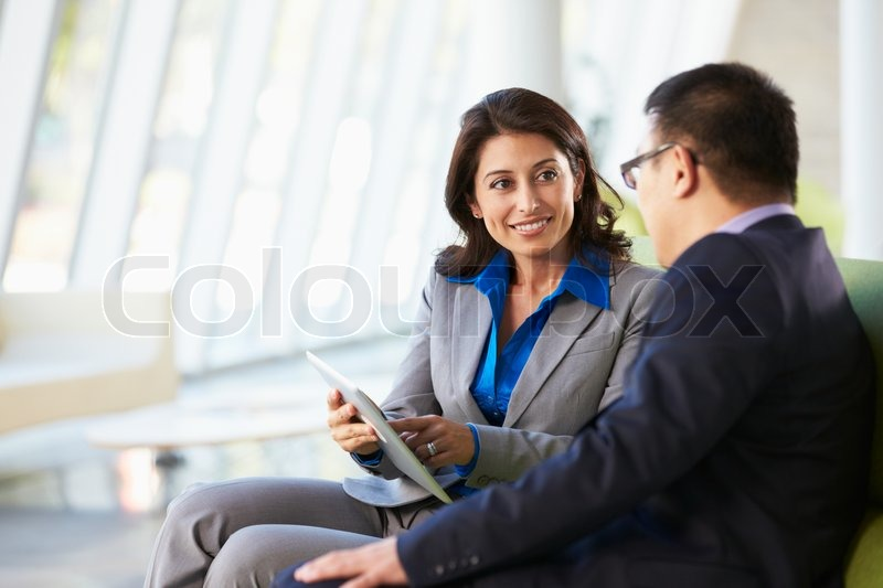 Businesspeople With Digital Tablet Sitting In Modern Office, stock photo