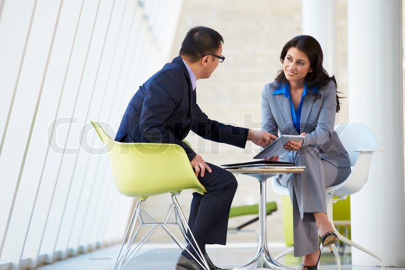 Businessman And Businesswoman Meeting In Modern Office, stock photo