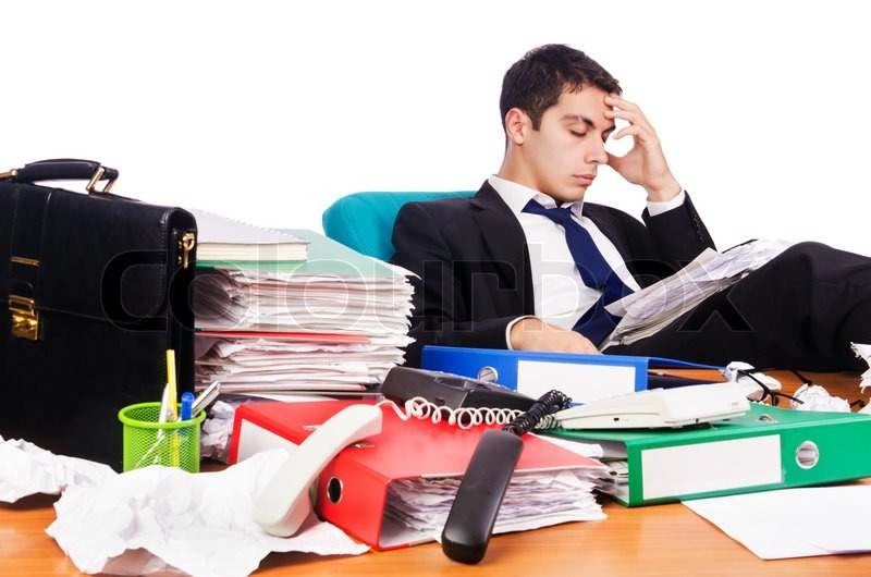 Stock image of 'Young busy businessman at his desk'