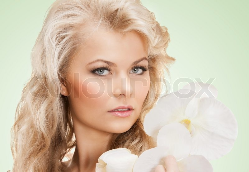 Stock image of 'Lovely woman with orchid flower'