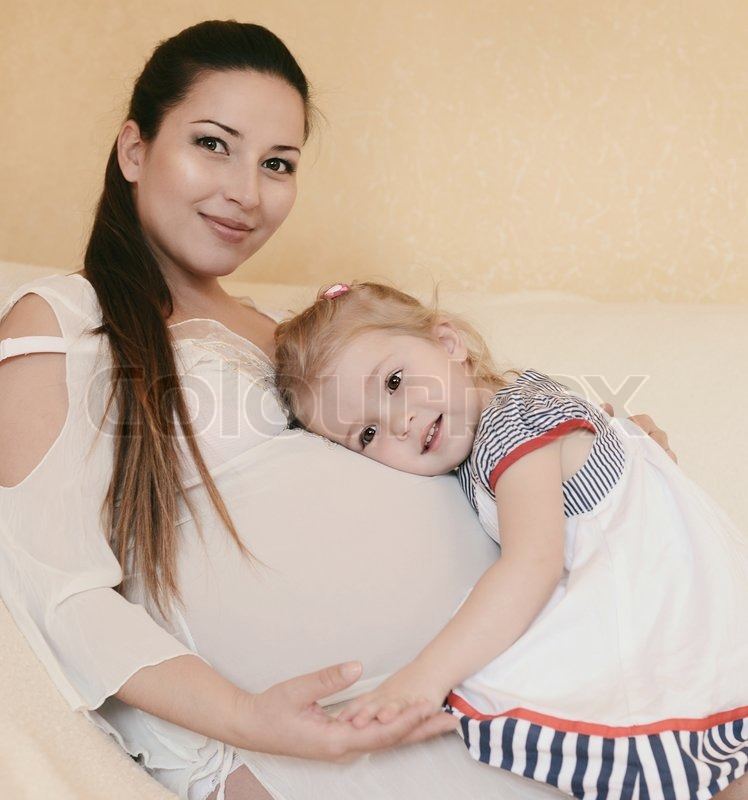Stock image of 'Pregnant mother with loving daughter'