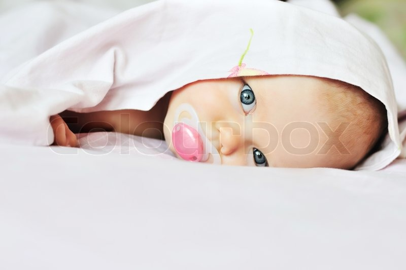 Stock image of '3 monthes old baby looking out under the blanket'